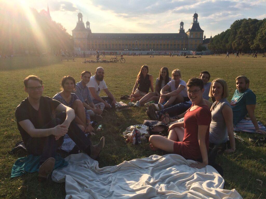 JEFer sitzen auf einer Picknickdecke im Hofgarten